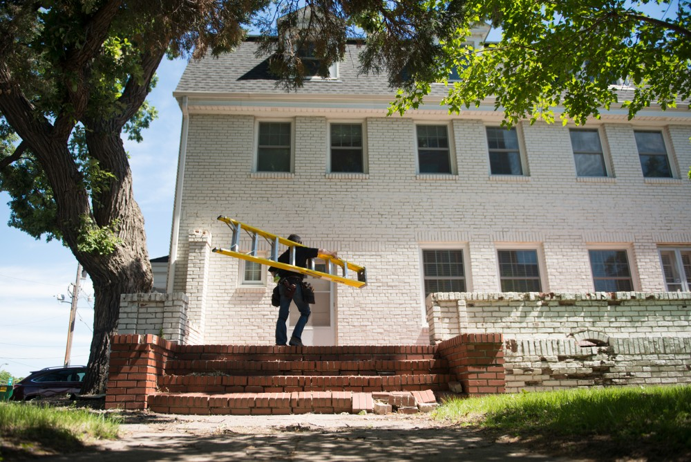 Electrician Curt Paumen prepares to install lights at the Gamma Phi Beta house as a part of Project Lighthouse on Tuesday, June 16.