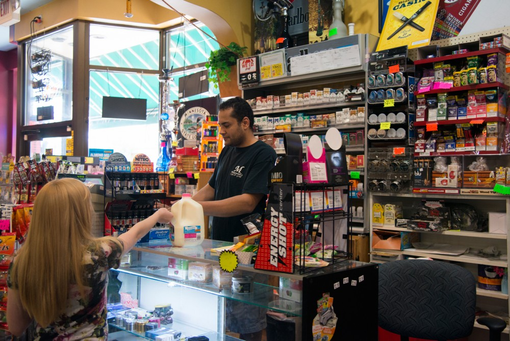 Manager Adam Hussein gives change to a customer at Maxwell's Market on Tuesday afternoon. Hussein believes the proposed restrictions on tobacco sales will hurt his business.
