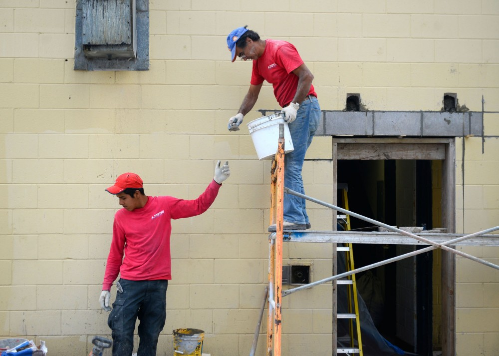 A. Pietig Concrete workers, Amaro and Ernesto Lima, work on constructing the foundation of a new patio at Library Bar in Dinkytown on Saturday. The new patio will be one of the largest in Minneapolis.