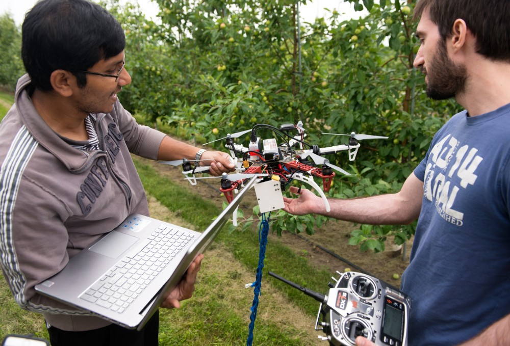 Parvakar Roy hands over drone to Graduate Student Nikolaos Stefas at University Arboretum on last Wednesday. A University group of undergraduates, graduates, and professors is in the process of developing a drone with the capability of aiding farmers by giving them information about their crops.