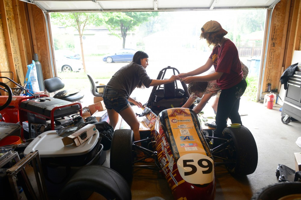 Justine Chu, Abby Hempy, and Alex Melin work on the Formula SAE car built by CSE group Gopher Motorsports in Minneapolis on Monday. The group members, who compete in the global Formula SAE series against other universities each year, often work on the car inside of a team members garage and are unhappy with the resources they have gotten from the University while building their vehicle.