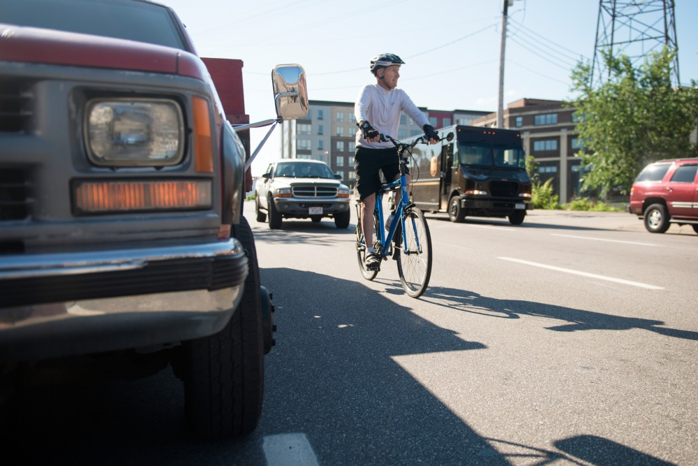 A biker moves into traffic to pass a vehicle illegally parked in the newly established bike lane on fourth street in Dinkytown on Tuesday, July 7. Though bikers now have a dedicated lane through Dinkytown, drivers continue to park within the lane illegally, causing safety issues with bikers who are forced to pass.