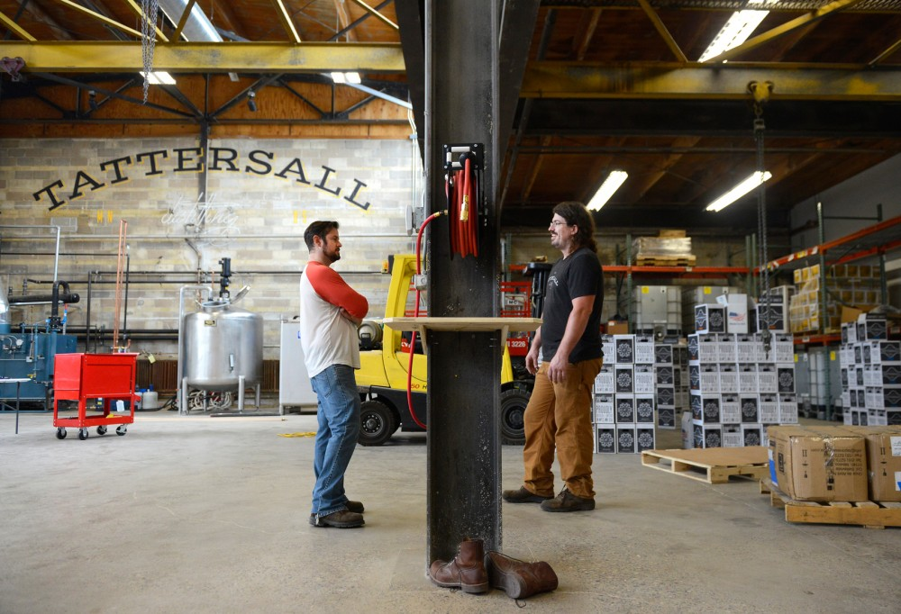 Founder Dan Oskey talks to Distillery Manager Bentley Gillman at Tattersall Distilling in northeast Minneapolis on Monday. Tattersall, which distills its own spirits in a distillery just beyond the glass walls of its cocktail room, will open for business on Wednesday, July 8.