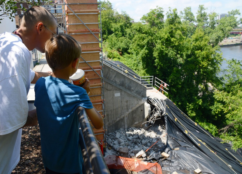 Minneapolis resident Jonathan Parish and his son, Jayden, view the damaged slope above West River Parkway on Monday afternoon. The area was affected by a mudslide last June and is being repaired this month.