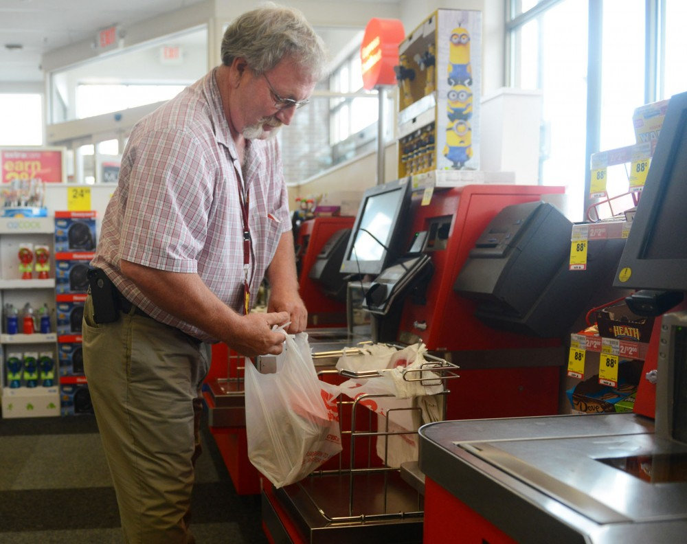 Paul Schoenecker places his purchased items in a plastic bag at CVS on Tuesday. Ward 2 City Councilman Cam Gordon hopes to reduce the city's environmental impact by keeping bags out of landfills and possibly banning plastic bags at retail sites throughout the city.