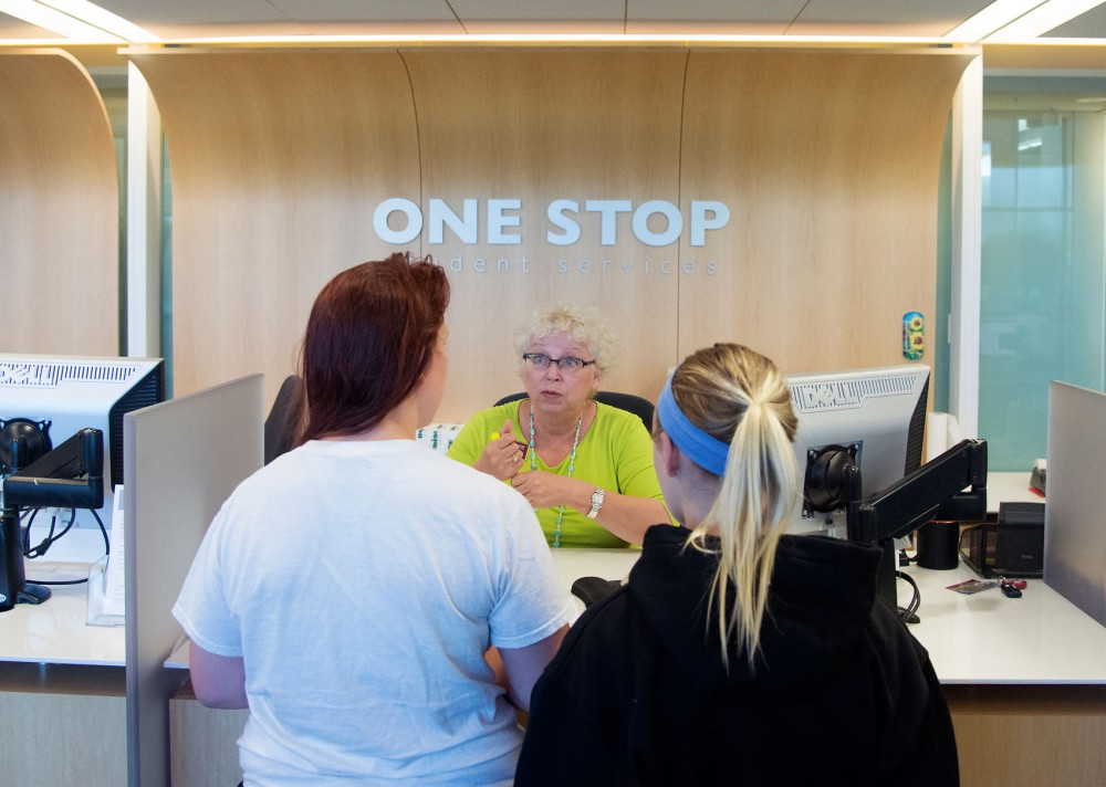 One Stop employee Rebecca Kroening helps two guests in Bruininks Hall on Thursday. This fall, One Stop will begin providing a new service where students can receive advice on personal finance.