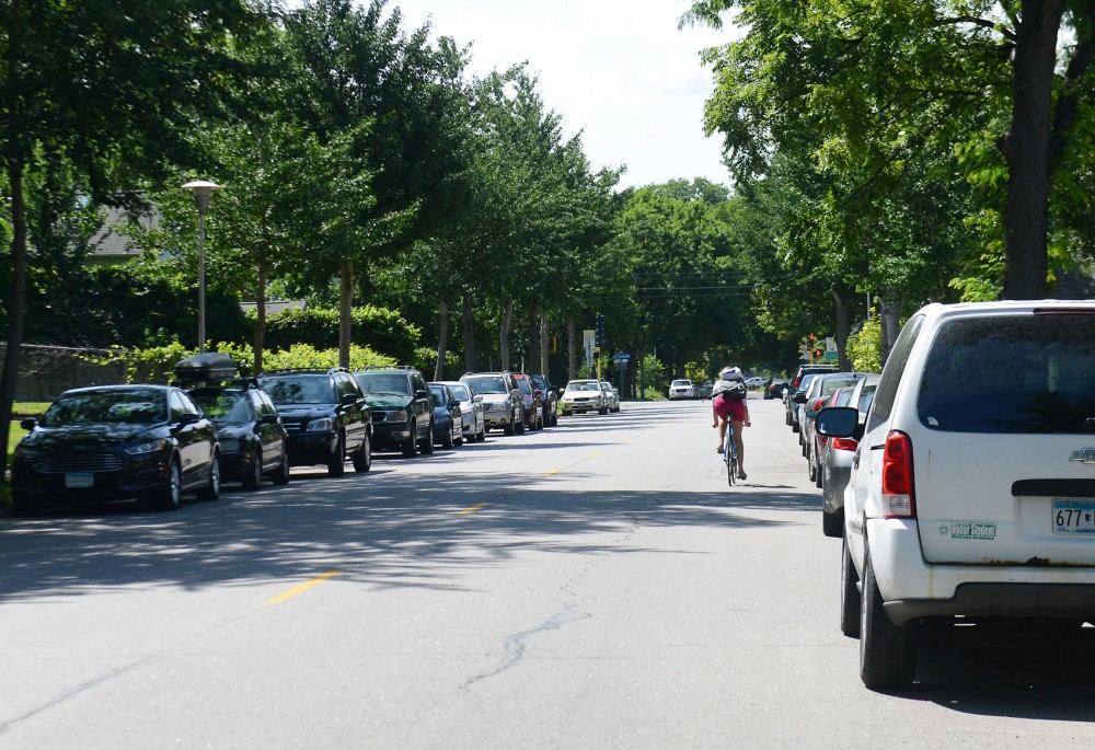 A biker travels along 18th avenue on Tuesday. While the city is planning to give the street bike lanes, the Southeast Como Improvement Association worries that such a change will harm parking availability in the highly populated area.