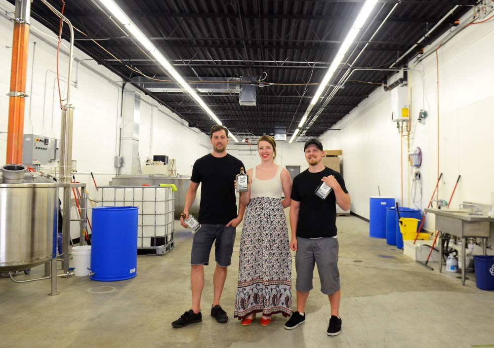 (Left to right) Nate Karnitz, Kirsten Karnitz and Chris Kulzer pose with their first product, Tippling House Vodka, at Lawless Distilling Company in St. Paul on Monday. Founder and Carlson School of Management graduate Nate Karnitz noticed the growing distillery scene in the Twin Cities and decided to start one of his own.