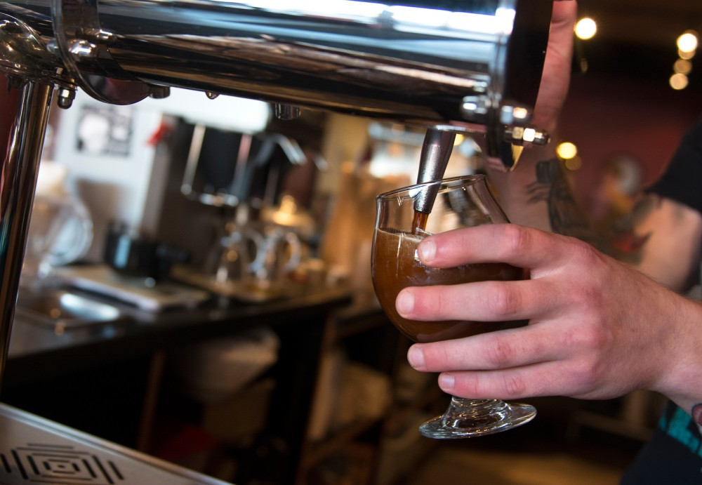 Barista Stephen Engler pours a fresh cup of Blackeye Roasting Company's nitro cold brew at Quixotic Coffee on Tuesday. Quixotic is one of the few stores that offers the cold brew on tap.