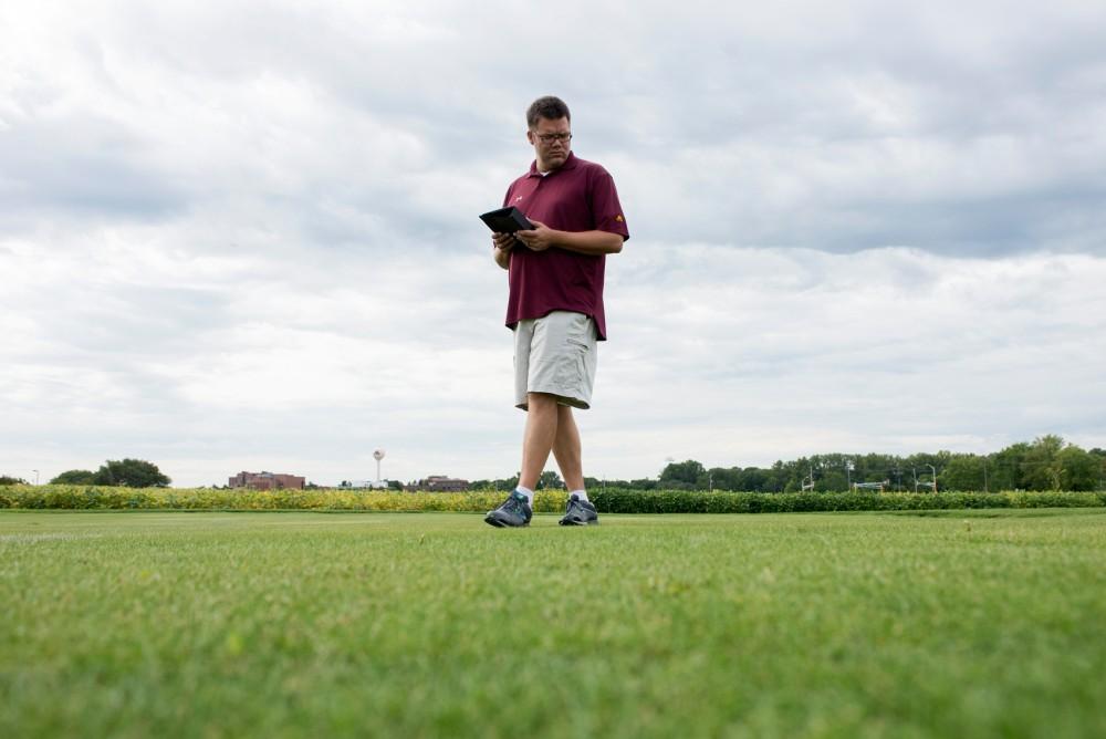 Associate Professor of turfgrass breeding and genetics Eric Watkins evaluates turf plots for disease resistance on Wednesday in St. Paul.