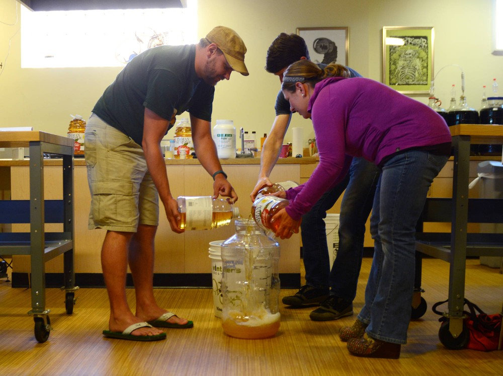(left to right) Emmet Swartout, Christian Breitbarth and Tia Houseman pour apple juice into a container at a Northern Brewer workshop as a part of the process for making hard cider on Saturday. Breitbarth guided the workshop and has led various other classes at Northern Brewer.