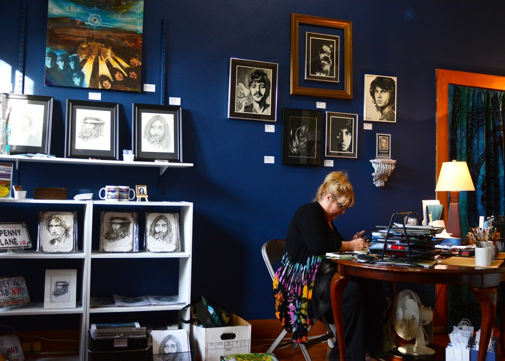 Sherri Faye, owner of Imagine Arts Studio, works on a comic strip piece on Saturday. The studio opened on September 10 and is currently showcasing original art and reproductions of iconic rock and roll pieces by various artists.