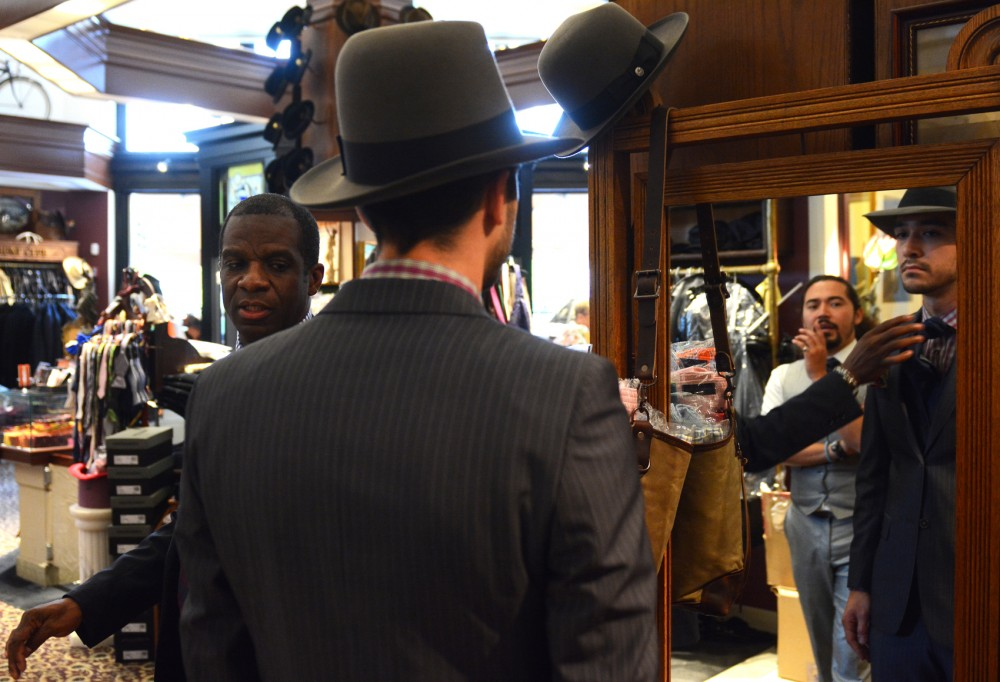 Jeffrey Barr looks in the mirror Monday while Keith Dorsett, manager of Heimie's Haberdashery, makes final adjustments to Barr's outfit at the Haberdashery store in St. Paul. The fitting was in preparation for the Homme Mens Fashion Show on Wednesday.