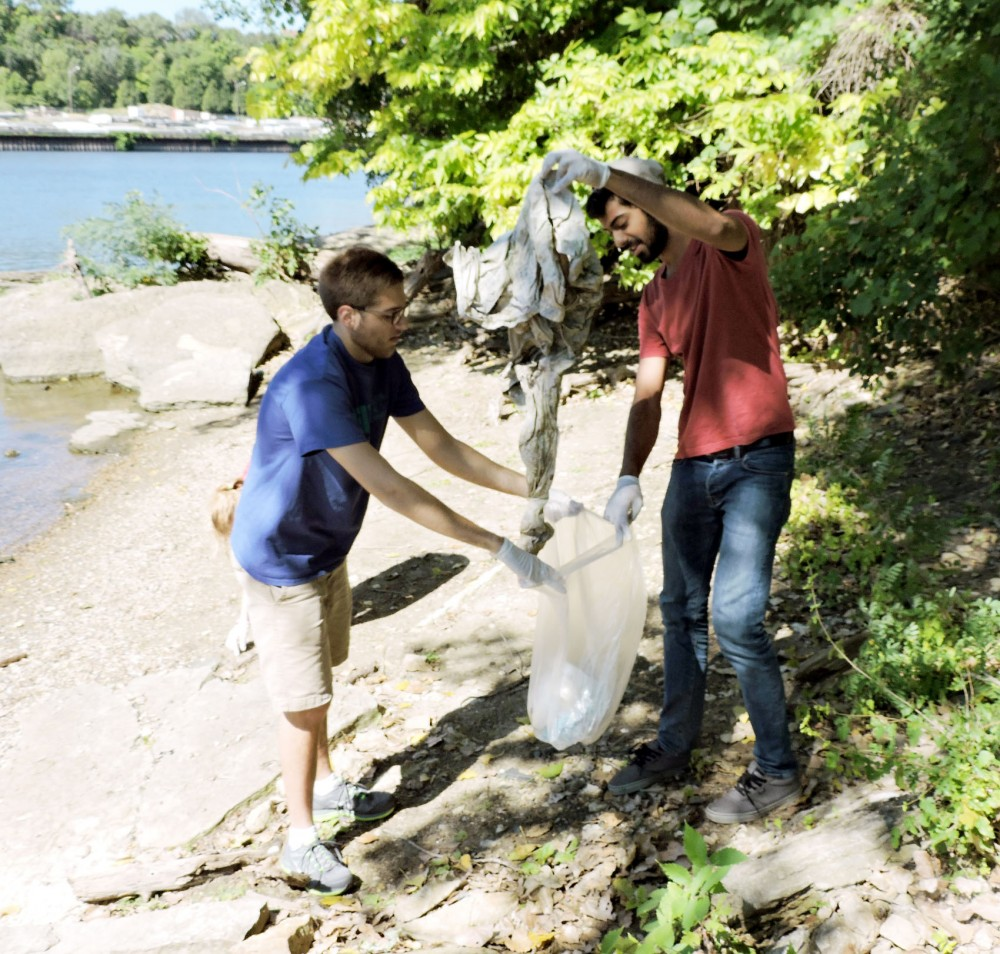 Neil Peterson, student involved in Lutheran Campus Ministry, Left, and Ahmed Siddiqui from the Muslim Students Association, pick up trash by the Mississippi River Sept. 13, 2015. The two student associations are working together to bridge the gap between Islam and Christianity and want to stimulate interaction through events this year with other religious groups on campus.