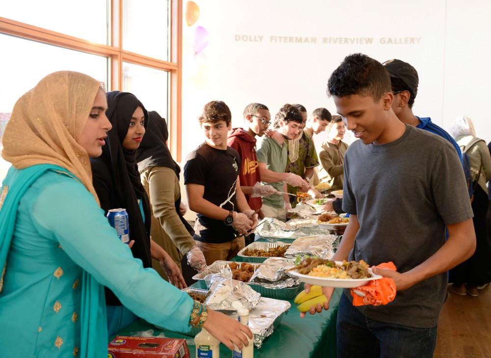 Freshman Moaaz Elmubark (right) gets food at the Al-Madinah Cultural Center hosted