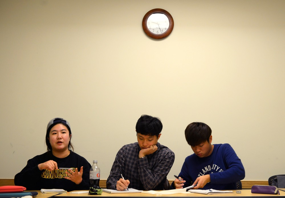 Korean Student Organization President Youngran Jung (left) engages in discussion Monday night in Moos Tower. This Fall, UMPD officer Sam Schooler was appointed as a liaison for Korean students, serving as a direct contact for helping them navigate the U.S. legal system as well as communicating safety messages.