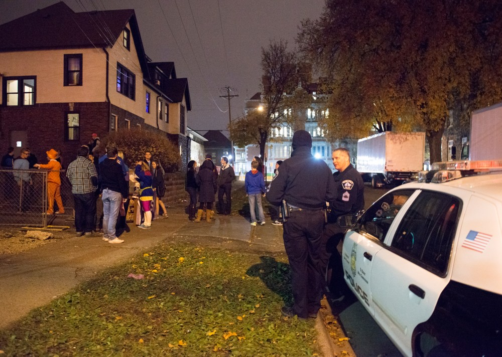 Minneapolis police officers look on as students enter the Riff Raff concert put on by Sigma Chi fraternity on Friday night. The event was staffed by 8 off-duty police officers, security guards, and members of the fraternity, in an effort to keep the event safe and crime free.