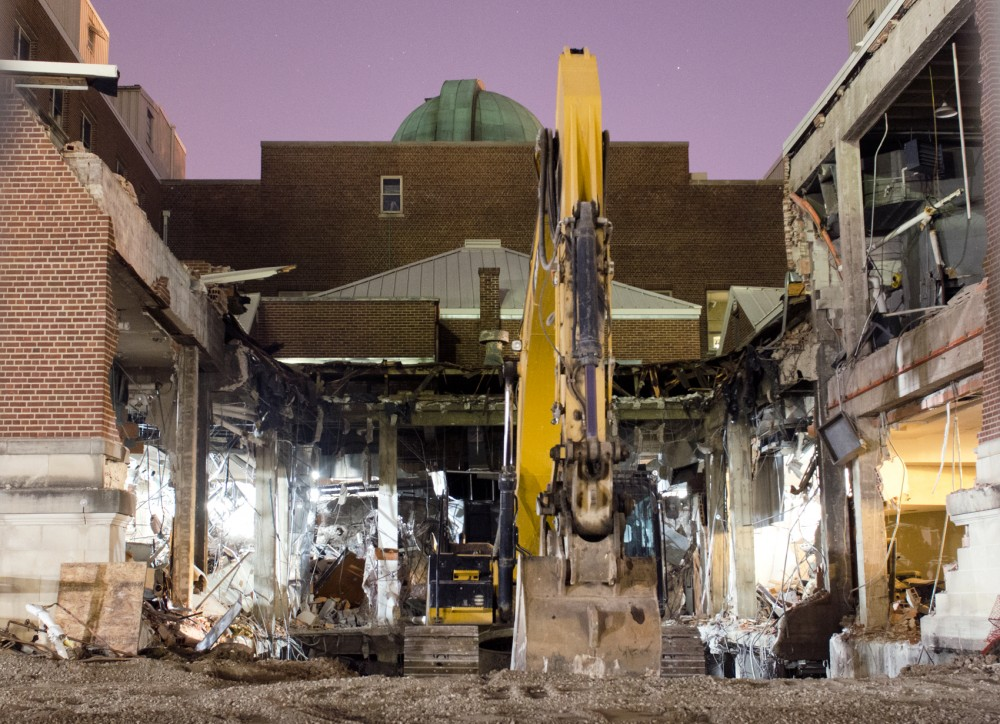 A backhoe sits in the dirt at the backside of the Tate Laboratory of Physics on Saturday evening. The renovation being done is part of a 92.5 million dollar project.