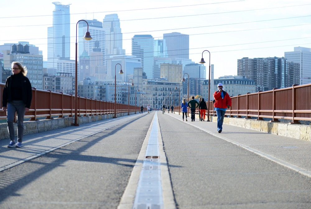 Pedestrians cross the Stone Arch Bridge on Tuesday. The city of Minneapolis' parks department will begin notifying people that photography and gatherings are not allowed on the bridge without a permit from the city.