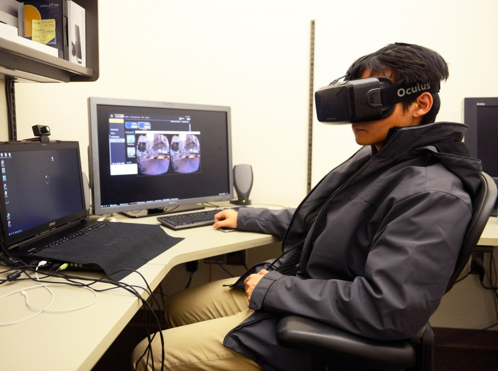 Virtual Reality Lab Manager Penh Liu demonstrates the Oculus Rift, a head-mounted virtual reality display in the in Walter Library on Monday. The Rift allows the user to play immersive games, watch 360° videos, and interact socially with other users.