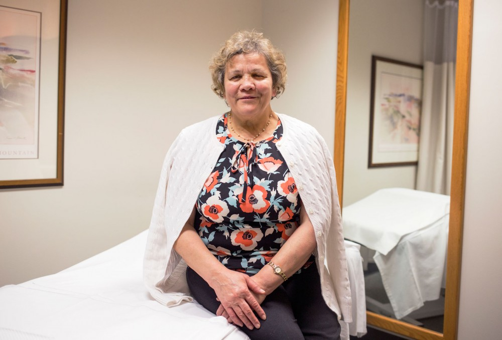 Coca-Iona Vladislav, a professional massage therapist at Boynton Health Service, sits posed on the massage table where she tends to her patients on Friday.