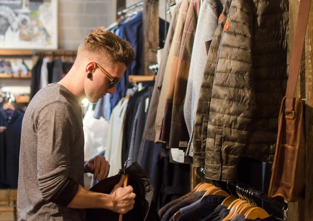 Jared Tuttle looks through various clothing options at Atmosfere in North Loop on Monday, selecting an outfit for the upcoming I Am MPLS fashion show tonight at First Avenue