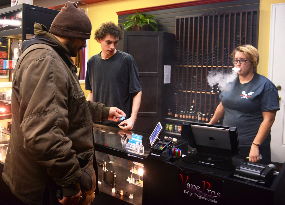 Vape Pro's Sales Associate Emily Bosacker, right, exhales vapor while working with Assistant Manager Joel Volden to help customer Jerome Norris, far left, purchase a replacement tank at Vape Pro's on University Avenue in St. Paul on Friday.