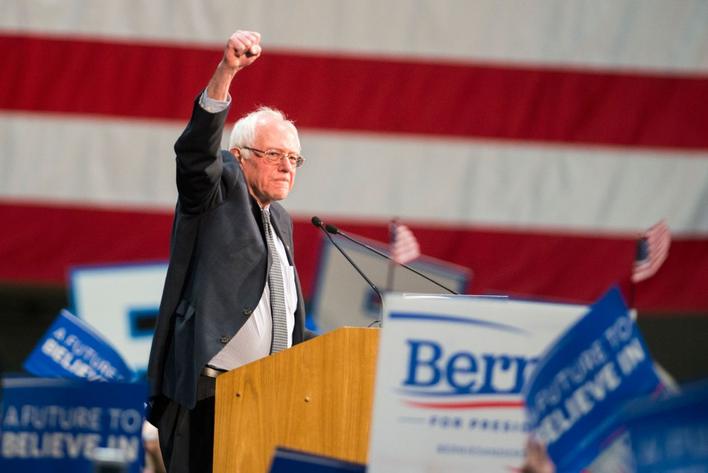 Democratic presidential candidate Bernie Sanders pumps his fist into the air, greeting a crowd of nearly fifteen thousand supporters who attended his rally at the St. Paul RiverCentre on Tuesday evening.