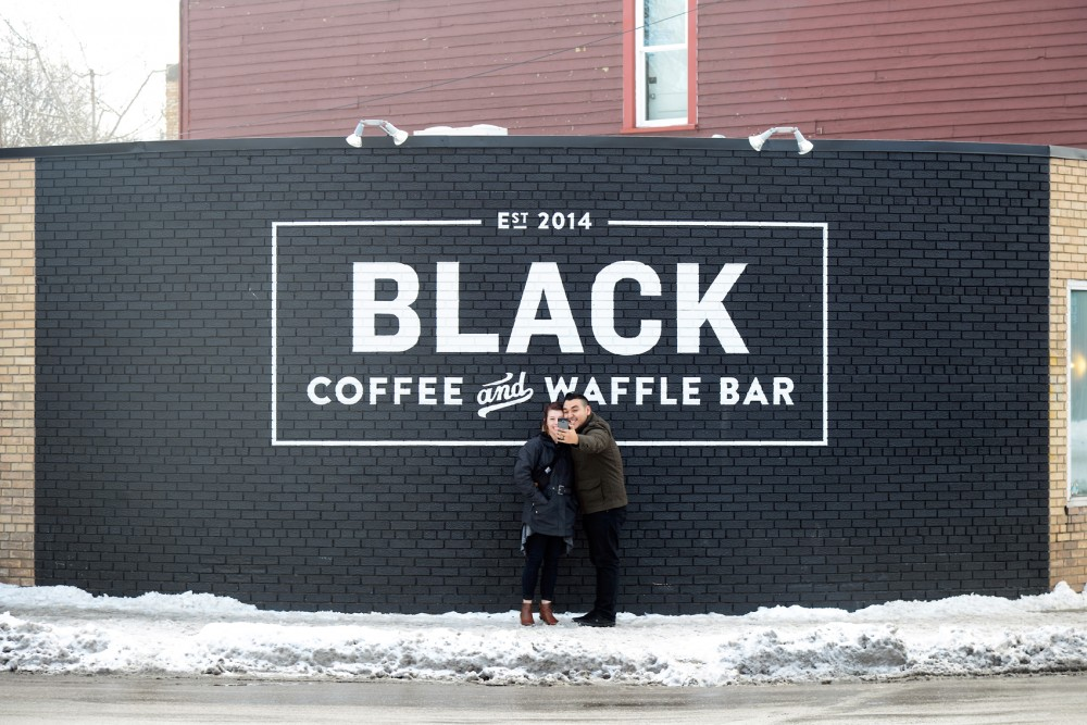 Mollie Galvez and her husband Wil take a selfie in front of Black Coffee and Waffle Bar on Saturday morning in Southeast Como after having breakfast. The store plans to expand with a new location in St. Paul set to arrive by April.