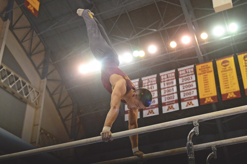 Freshman Justin Karstadt competes on the parallel bars at the Sports Pavilion on Saturday night, where the Gophers came in 2nd out of six competing teams.