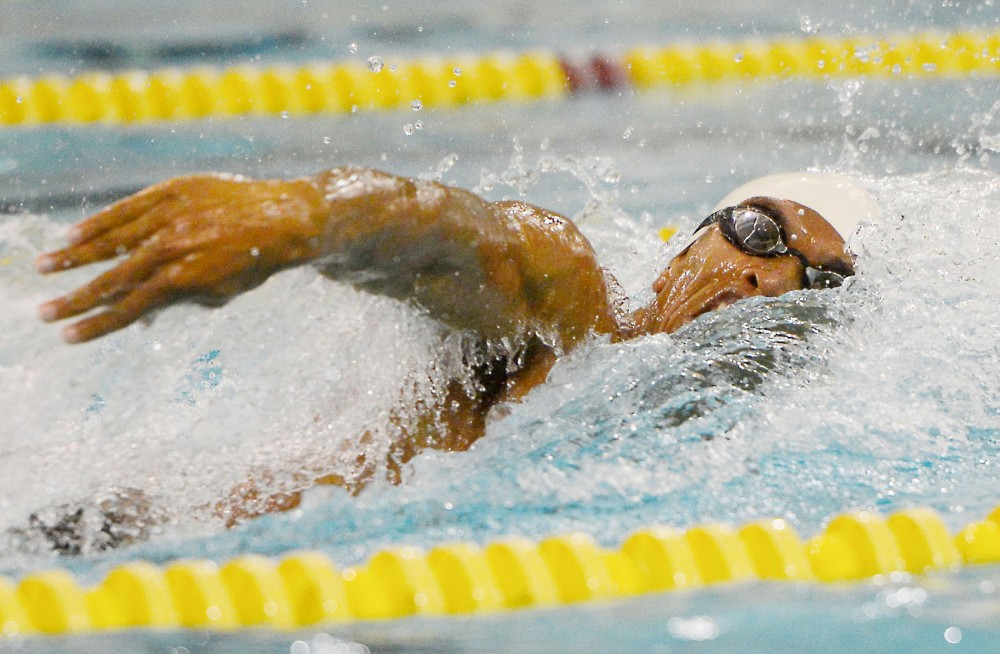 Junior Daryl Turner charges ahead, dominating the 100 freestyle at the Aquatic Center on Oct. 24, 2014, against North Dakota. Turner took first place and finished with a time of 44.75.