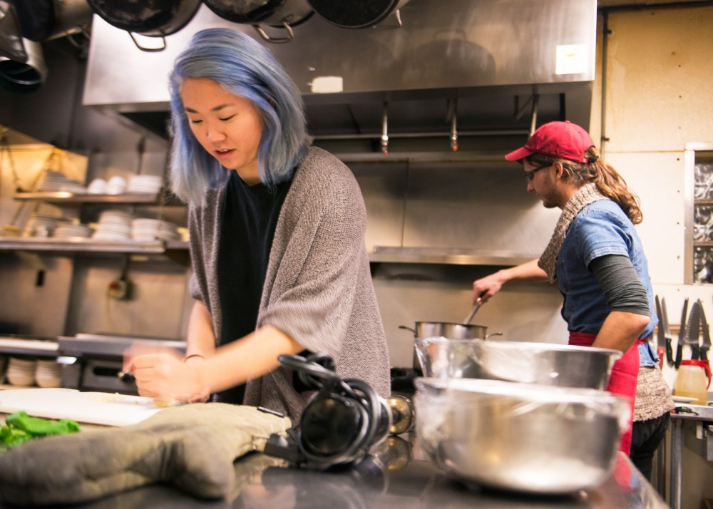 Minnesota Daily reporter Yena Lee crushes a clove of garlic as kitchen staff member Currant prepares a vegan tomato basil soup on Tuesday evening at Seward Cafe in Minneapolis.