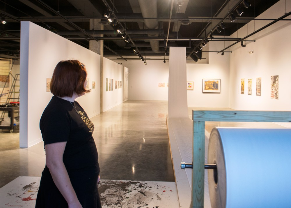 Co-curator Jenny Schmid looks over the space at the