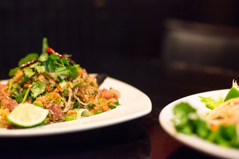Nam-Khao and papaya salad sit on a table Tuesday at On's Kitchen in St. Paul. Nam-Khao, a more traditional thai dish, features spiced rice, sausage, peanuts and coconut in a lime vinaigrette.