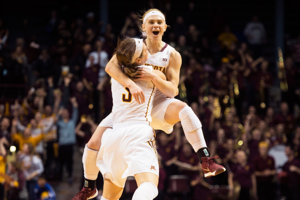 Sophomore guard Carlie Wagner jumps into the arms of teammate Shayne Mullaney after her game-winning shot in overtime against Ohio State in Williams Arena on Wednesday night.