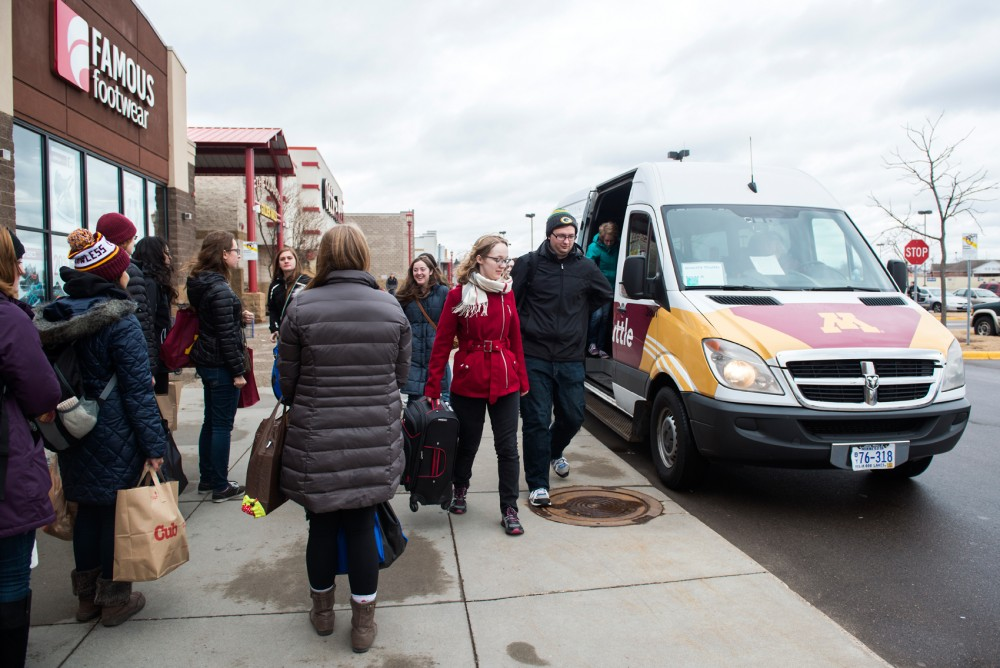 Grocery-laden University students wait to climb aboard the grocery shuttle during its Sunday pilot-day launch, while others exit to go shopping at Cub Foods at the Quarry in Northeast Minneapolis.