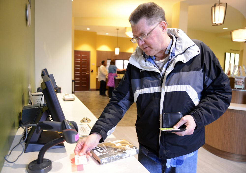 Gordon Folke checks out a book at the George Latimer Central Library in downtown St. Paul on Wednesday. On Tuesday, the Metropolitan Library Service Agency implemented a new program that allows people with library cards access to certain museums and theaters for free or discounted prices.