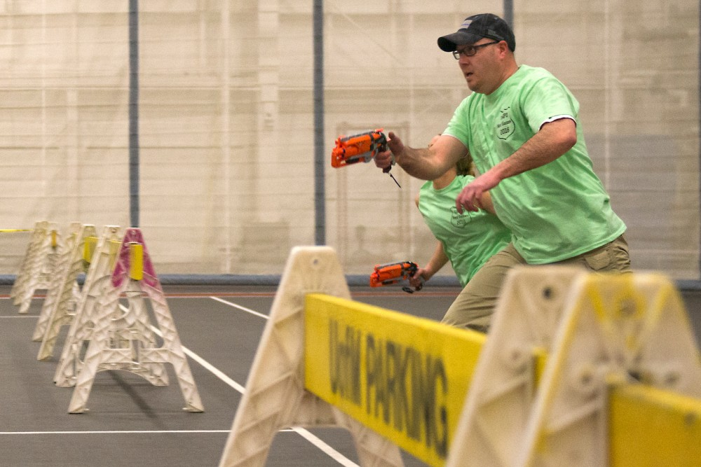 UMPD Sgt. Tom Bohrer races towards enemy territory at NERF Games Wednesday at the University Fieldhouse. Groups of 6-8 paired up with an officer to compete against each other in a game of NERF capture the flag.