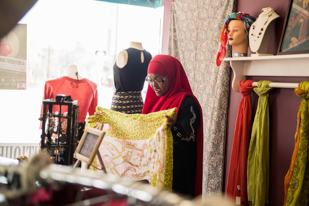Fatuma Mohammed speaks to a customer at Sisterhood Boutique on West Bank on Monday. The store was created by East African women in the Cedar-Riverside neighborhood in an effort to provide girls ages 14-21 with work experience through an intern program, which Mohammed was a part of before becoming an employee.