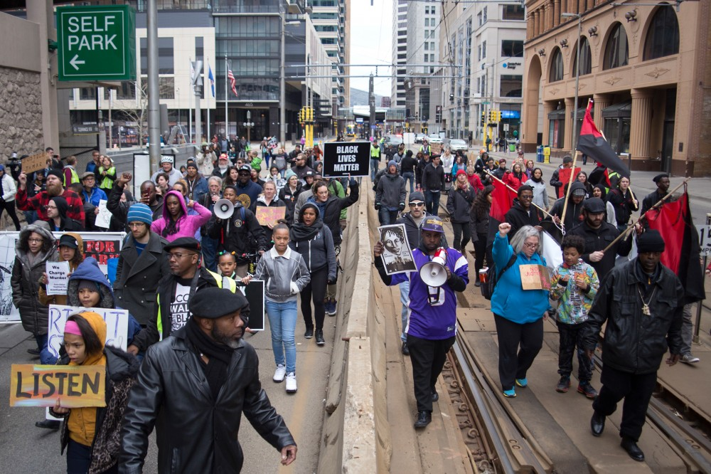 Demonstrators march on the tracks of the light rail through downtown Minneapolis on Saturday following a rally outside of the Hennepin Country Government Center. 