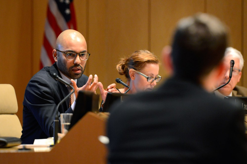 Universit of Minnesota regent Abdul Omari responds to student representatives Cory Schroeder and Callie Livengood about the proposed tuition hike for out of state students during the board of regents meeting in the Mcnamara Alumni Center on Thursday morning.