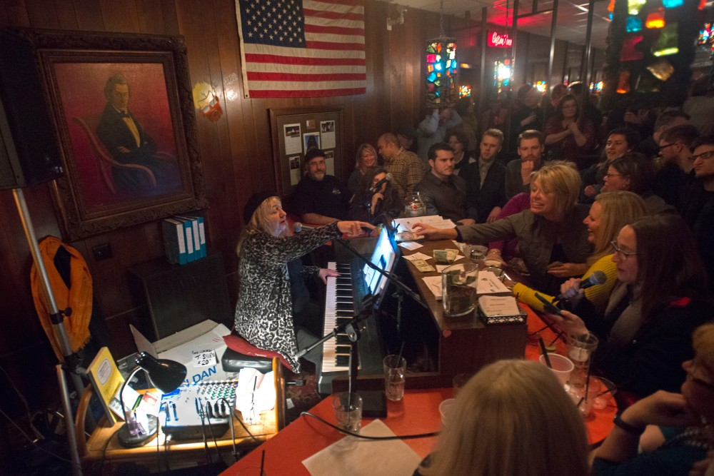 Patrons crowd around Daina De Prez while she performs at Nye's Bar and Polonaise room Saturday evening. The Bar will be closing after 67 years and will be holding its last polka dance on Sunday April 3.