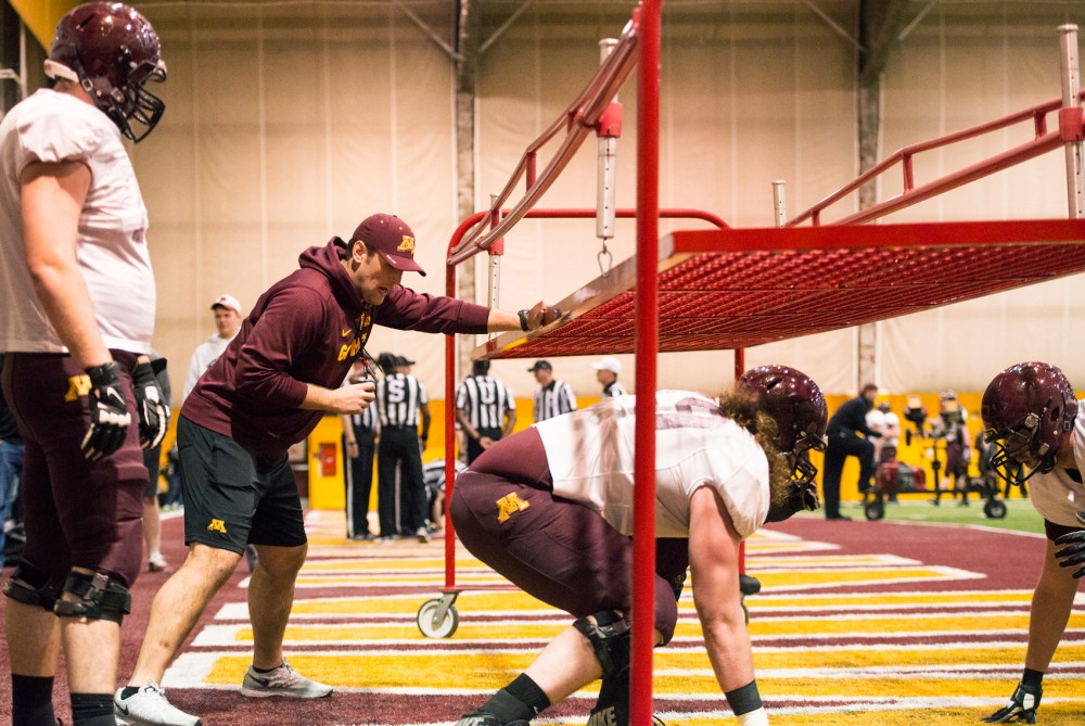 Offensive line coach Bart Miller runs Gopher players through a drill during their Spring Practice on Saturday morning.