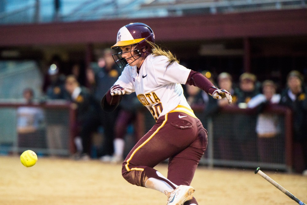 Freshman Maddie Houlihan throws her bat after a base hit against Wisconsin on April 12 at Jane Sage Cowles Stadium.