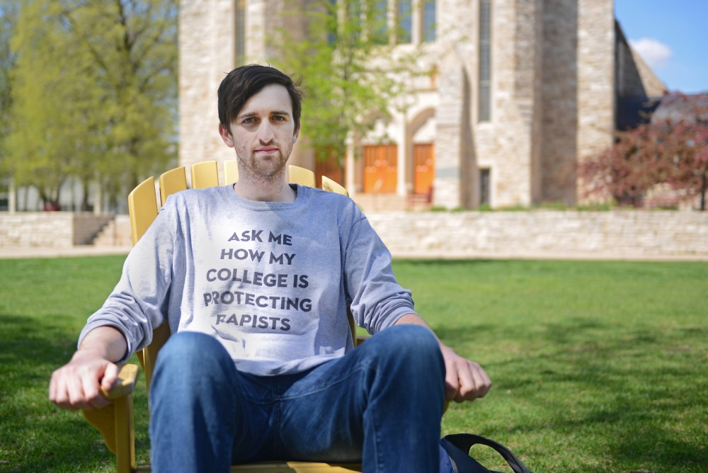 Senior Doug Carmody sits on the St. Olaf campus wearing his shirt that reads