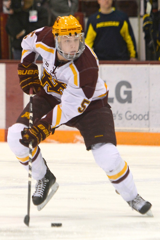 Minnesota defenseman Mike Reilly controls the puck against Michigan at Mariucci on Feb. 14, 2014.