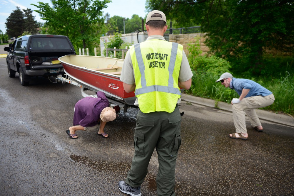 Watercraft Inspector Jack Kronberg, along with the boat owners, inspect a boat for invasive species before it enters the water at Grays Bay on Lake Minnetonka on Memorial Day.