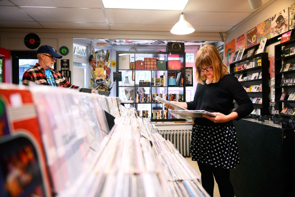 Volunteer Lauren Haun organizes vinyl records for sale at Dead Media, an independently run cassette, record and bookstore in the Seward neighborhood, on Monday June 6.