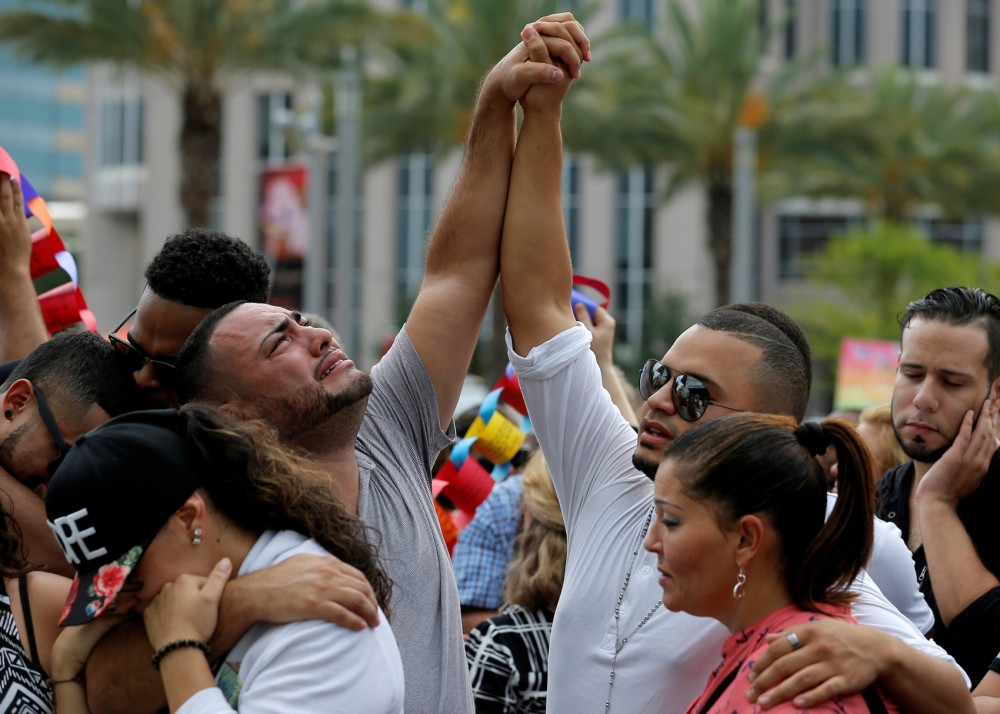 Mourners grieve at a vigil for the victims of the shooting at the Pulse gay nightclub in Orlando, Florida, June 13, 2016.