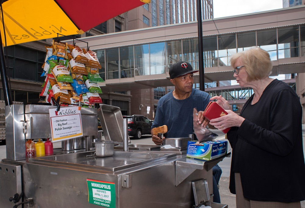 Jimmy Young, a Nibbles hotdog food cart operator prepares a hotdog for a customer in downtown Minneapolis on the afternoon of 27 June. The Minneapolis City Council ruled to change an ordinance that had previously restricted the operating area of food carts.
